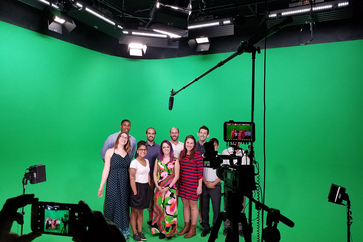 Group of men and women in front of green screen